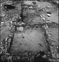 Room 8 in foreground, facing west. Note overturned metate and slab in corner hearth. (BW-YJ-JC-008)